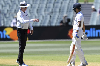 India's Virat Kohli is held up by umpire Paul Reiffel as the third umpire checks the catch.