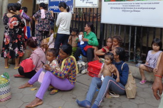 Families of sick children are queued up outside the gates of Phnom Penh's Kantha Bopha hospital.