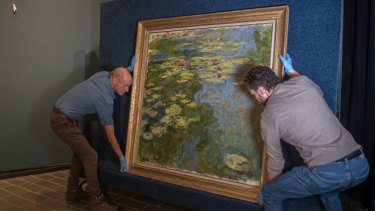 National Gallery of Australia installers Ben Taylor (left) and Chris Burton hang Monet's Water Lilies.