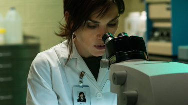 Nancy Jaax (Julianna Margulies) looks at samples in a microscope in her pathology lab.