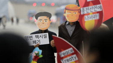 Protesters wearing masks of Donald Trump and Kim Jong-un stand during a rally demanding the denuclearisation of the Korean Peninsula and peace treaty near the US embassy in Seoul, South Korea, on Thursday.
