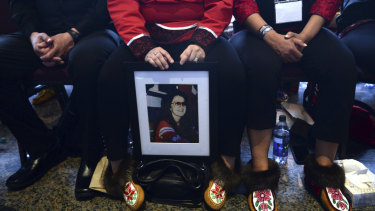 A woman holds a photo of a lost family member at the closing ceremony for the inquiry.