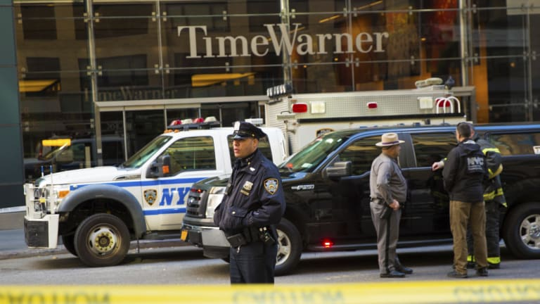 An officer keeps watch in front of the Time Warner Building after an explosive device was removed in October.