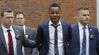 Actor Cuba Gooding Jr., centre, is led by police officers from the New York Police Department's special victims division.