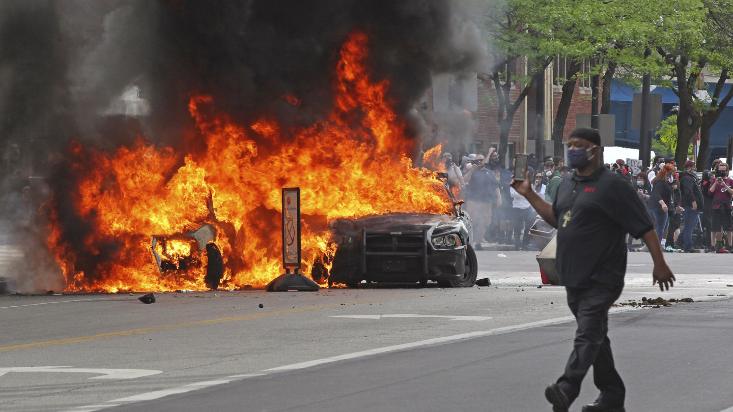 People watch as a Cleveland police cruiser burns  during a protest on Saturday seeking justice in the death of George Floyd.