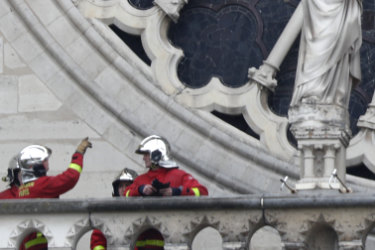 Firefighters assess Notre-Dame's famous rose window after the fire.