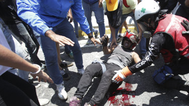 A man who was run over by a Bolivarian National Guard vehicle is aided by fellow anti-government protesters outside La Carlota airbase.