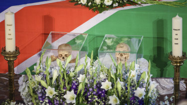The skulls of two people killed in the  the Herero and Nama uprising between 1904 and 1908 are flanked by candles during a ceremony in Berlin in August.