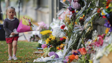 A girl carries flowers to a memorial wall following the mosque shootings in Christchurch, which left 50 dead and 39 wounded.