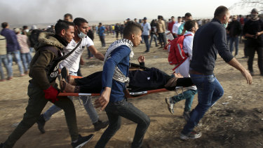 Palestinian protesters evacuate a wounded woman during clashes with Israeli troops along Gaza's border with Israel on Friday.