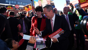 Bill Shorten high-fives a boy while on the last-minute campaign trail with Labor's candidate for Higgins, Fiona McLeod.