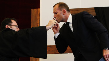 Then prime minister Tony Abbott kissing a crucifix held out by Bishop Antoine-Charbel Tarabay at a Good Friday church service.