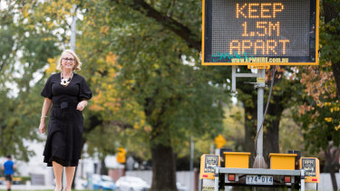 Melbourne lord mayor Sally Capp yesterday next to a sign urging social distancing.