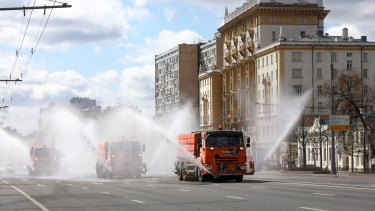 Tankers spray disinfectant on the empty Garden Ring in Moscow on Sunday, with the US embassy on the right.