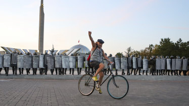 A protester rides a bicycle in front of police during an opposition rally to protest against the presidential inauguration in Minsk, Belarus.