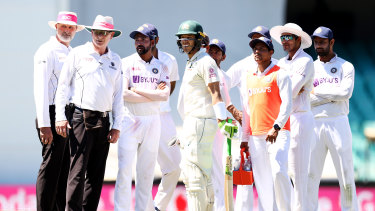 Australia captain Tim Paine stands with Indian players and umpires as police walk six men from their seats during the third Test.