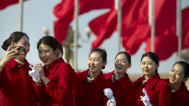 Bus ushers react as they pose for a selfie during a meeting one day ahead of the opening session of China's National People's Congress at the Great Hall of the People in Beijing.