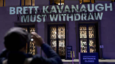 "The words ""Brett Kavanaugh Must Withdraw"" are projected by demonstrators onto the E. Barrett Prettyman United States Courthouse in Washington, DC."
