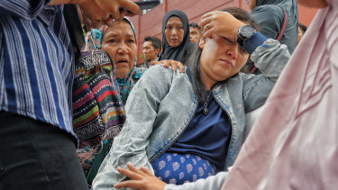 Putri Pratiwi covered her eyes crying over her husband and son, who were on Lion Air flight JT610.