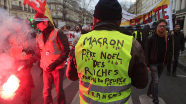 "A Yellow Vest protester attends a demonstration in Paris on Thursday. His vest says ""Macron, Father Christmas to the rich, enemy of the French people""."