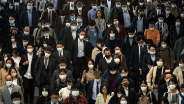 Commuters, mostly wearing face masks, walk through Shinagawa train station, Tokyo, on Wednesday.