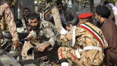 Iranian armed forces members and civilians take shelter from the  shooting.