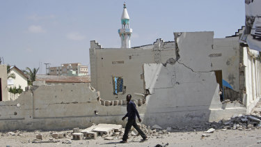 A man walks past destroyed buildings after a large blast in  Mogadishu, Somalia, on December 22.