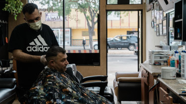 Omar, who is from Lebanon and  part-owner of Joe's Hair Cut in El Cajon, cuts a customer's hair.