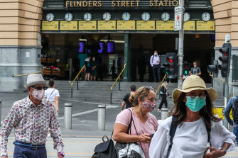 People wearing masks walk past Flinders Street Station on Thursday.