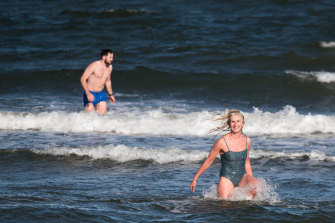 Natasha Herbert and Tony Masterton brave freezing conditions at St Kilda beach for a dip last week.