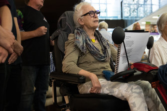 """I wouldn't miss it for the world"": Judith Maher sings along in her mobility scooter."