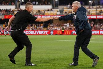 Tigers coach Damien Hardwick and Lions counterpart Chris Fagan bump fists at the Gabba.