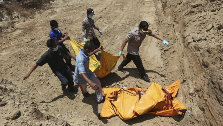 Indonesian rescue team members carry the body of a victim to a grave during a mass burial in Palu on Monday.