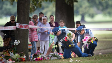 Police gather flowers left for the victims and hang them on the fence of the mosque on Tuesday.