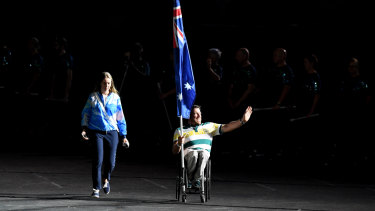 Kurt Fearnley carries the Australian flag into the closing ceremony on Sunday night.