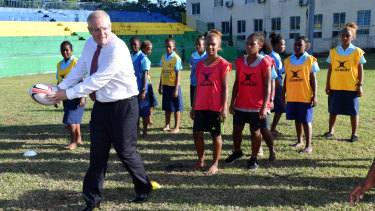 Prime Minister Scott Morrison plays rugby with students in Honiara, Solomon Islands, on Monday.