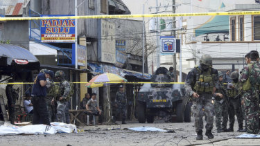 Police investigators and soldiers attend the scene in Jolo on Sunday.