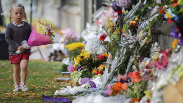 A girl carries flowers to a memorial wall following the Christchurch shootings, which left 50 dead and 39 wounded.