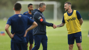 Keeping busy: The suspended Roy O'Donovan shakes hands with Newcastle Jets coach Ernie Merrick at training.