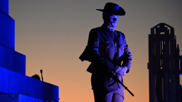 A soldier stands guard by the State War Memorial in Kings Park as the sun slowly rises over Perth.
