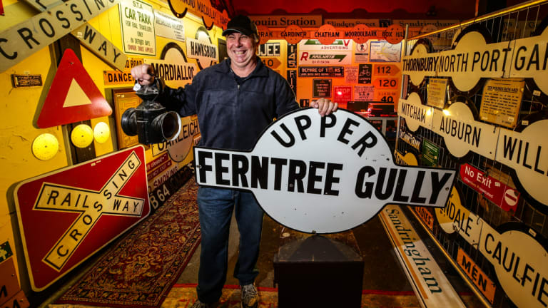 Graham Dann, pictured at Yarra Valley Auctions, with the station sign he drove for three hours to buy and a vintage railway lantern.