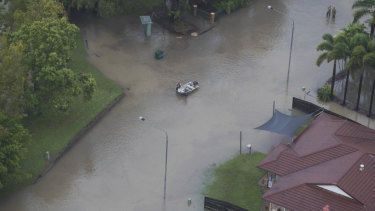 Residents leading a tinny through a flooded street in Townsville on Monday.