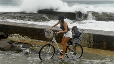 A woman negotiates a flooded path at Snapper Rocks on the Gold Coast as huge swells and high tides are set to pummel south-east Queensland and far-northern New South Wales beaches over the coming days.