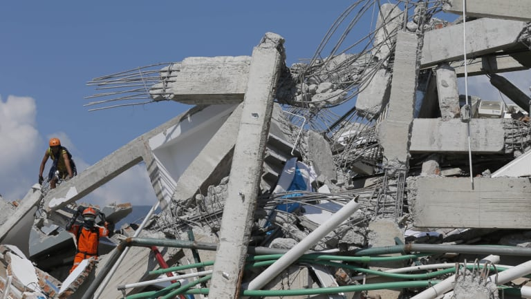 Rescuers search for people in the ruins of Roa-Roa Hotel in Palu on  Monday.