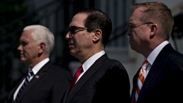Vice President Mike Pence, Treasury Secretary Steve Mnuchin and director of the Office of Management and Budget Mick Mulvaney, watch on as Trump celebrates the economy.