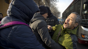 Plainclothes security officers take away a supporter of Chinese human rights lawyer Wang Quanzhang near the Secondary Intermediate People's Court of Tianjin.