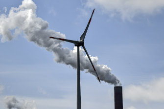 A coal-fired plant chimney and a wind farm.