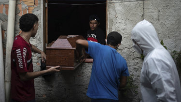 Relatives help a funeral worker, wearing protective gear, remove a body from a home in Manaus, Brazil, last year.