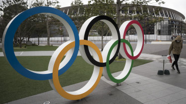 A man wearing a face mask walks past the Olympic rings in front of the main stadium for the Tokyo Olympics.