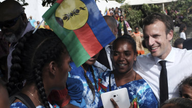 French President Emmanuel Macron, right, meets residents, one with the independence Kanak flag in her hair.